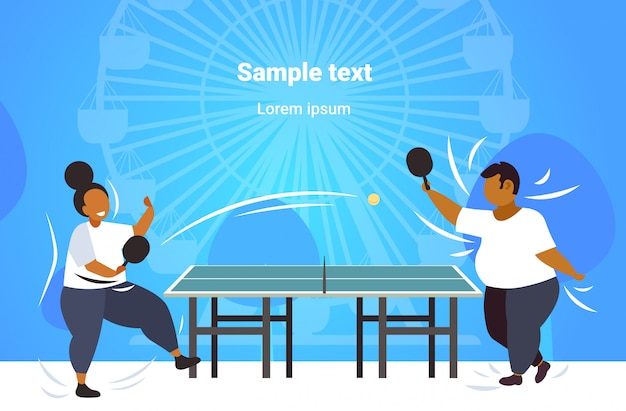 Fat obese couple playing ping pong table tennis african american overweight man woman having fun weight loss concept public park ferris wheel copy space Premium Vector