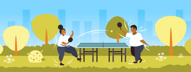 Fat obese couple playing ping pong table tennis african american overweight man woman having fun weight loss concept public park landscape Premium Vector