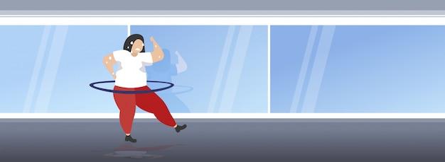 フラフープ太りすぎの汗女性カーディオトレーニングトレーニング減量コンセプト全長モダンなジムスタジオインテリア水平をねじる脂肪肥満の女の子 Premiumベクター