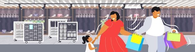 一緒に歩いて楽しいショッピングバッグ家族を保持している子供を持つ脂肪肥満の親休日大きな販売肥満コンセプトモダンなブティックファッションショップインテリアポートレート Premiumベクター