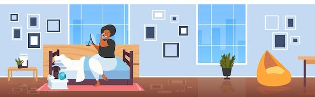 タッセルを使用してプロのメイクアップモダンなベッドルームのインテリアフルレングスの水平を作るミラーに触れるまつげを見て黒いマスカラーアフリカ系アメリカ人の女の子を適用する太った肥満女性 Premiumベクター