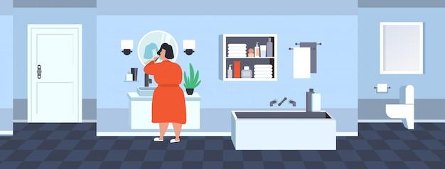 太った肥満の女性が歯を磨く太りすぎのアフリカ系アメリカ人の女の子がミラー肥満コンセプトモダンなバスルームインテリア全長リアビュー水平を見て歯ブラシを保持 Premiumベクター