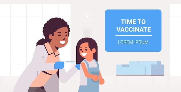 Женский доктор педиатр давая вакцинею впрыску снятый времени маленькой девочки для того чтобы вакцинировать концепция микстура медицинско concept экземпляр космос Premium векторы