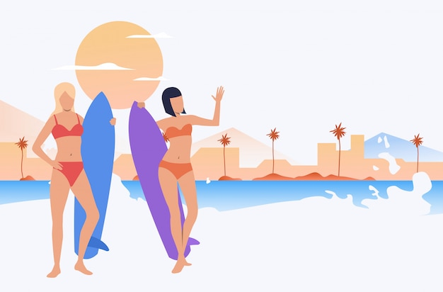Female friends in swimsuits standing on beach Free Vector