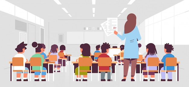 Female teacher holding tests with good a grade rear view pupils group sitting in classroom during lesson teaching education concept modern class room interior Premium Vector