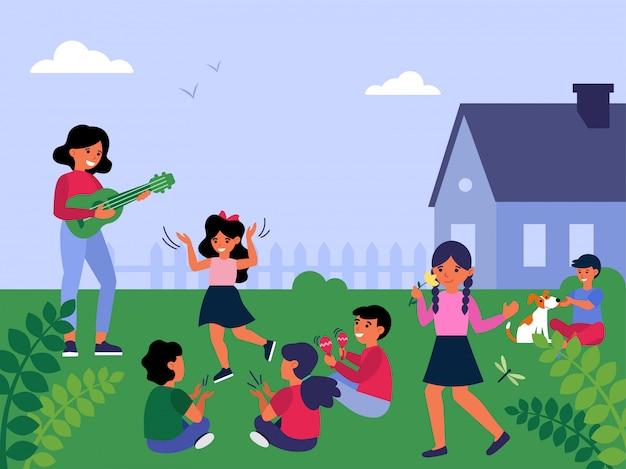 Insegnante di sesso femminile suonare la chitarra per bambini che giocano fuori Vettore gratuito