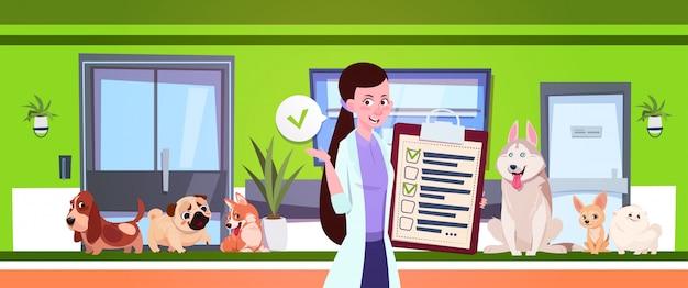 獣医診療所の待合室に座っている犬の上の女性獣医 Premiumベクター
