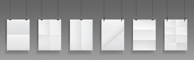 Сложенные пустые плакаты висят с зажимами для бумаг, листы белой бумаги с перекрещивающимися складками и держатели. Бесплатные векторы