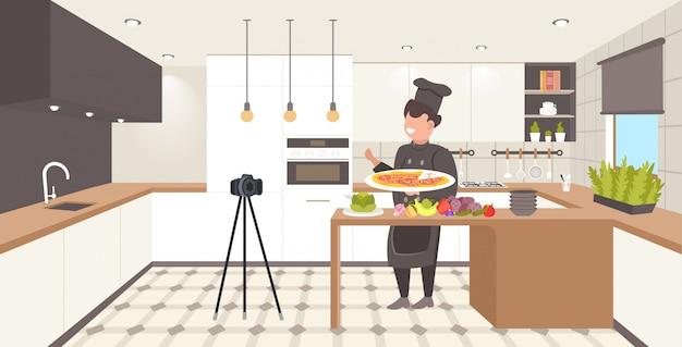 キッチンでシェフの制服を着たフードブロガー男性シェフシェフ三脚ブログコンセプトビデオブログのビデオブログを記録する料理を調理する方法を説明する男vlogger水平方向の完全な長さ Premiumベクター