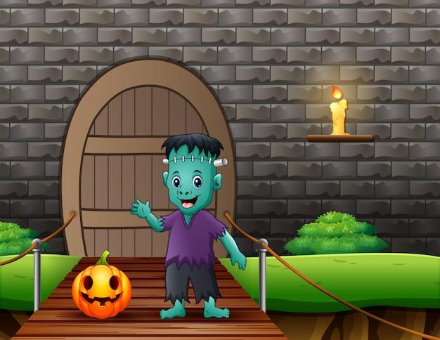 Frankenstein cartoon with a pumpkin on suspension bridge Premium Vector