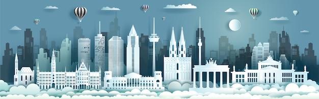 Архитектура германии туристические достопримечательности берлина с воздушными шарами и самолетом, тур по городу с панорамным видом и столицей, стиль вырезки из бумаги. Premium векторы