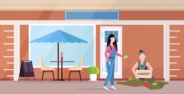 Девушка дает деньги грустной женщине нищий держит табличку с голодным текстом девушка бродит просят о помощи бездомные концепция кафе здание экстерьер квартира полная длина горизонтальный Premium векторы