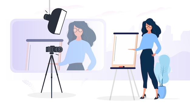 The girl is giving a presentation in front of the camera. the teacher conducts a lesson online. the concept of blogs, online training and conferences. camera on a tripod, softbox. Premium Vector