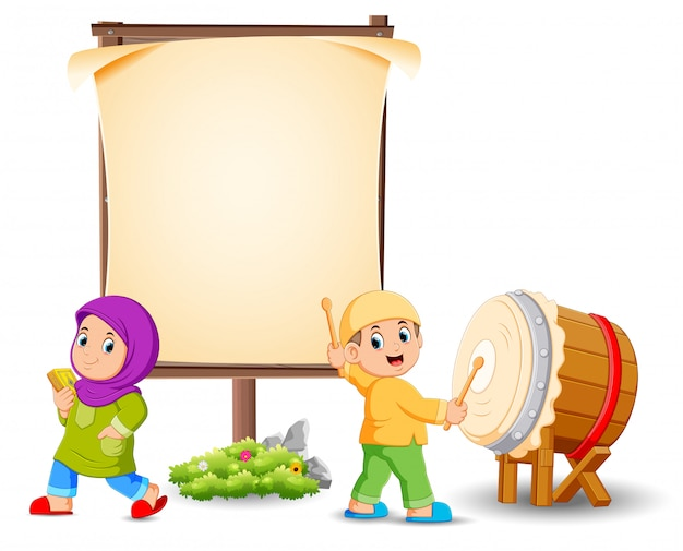 The girl is posing near the blank frame and the boy is hitting the drum Premium Vector