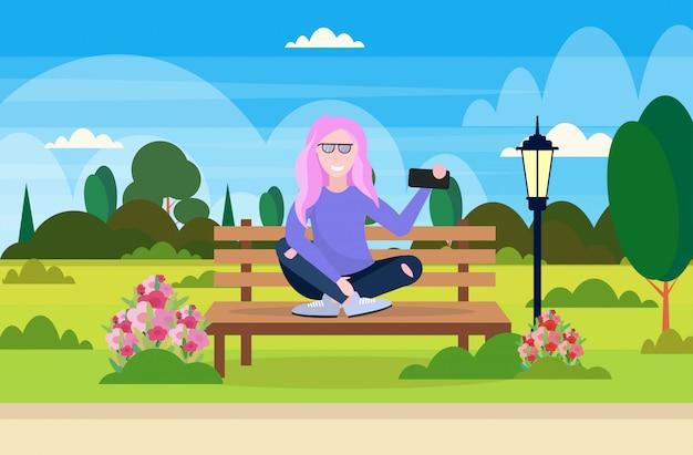 スマートフォンのカメラでselfie写真を撮っている女の子木製のベンチに座っている女性屋外公園の風景の背景女性漫画のキャラクター全長水平ベクトルイラスト Premiumベクター