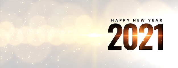 Glowing happy new year 2021 on bokeh light effect Free Vector