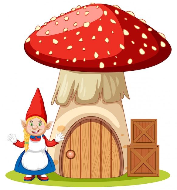白い背景の上のキノコの家の漫画のキャラクターの横に立っているノーム 無料ベクター