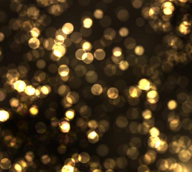 ゴールドのボケは黒い背景にぼやけた光。黄金色のライト抽象的なキラキラ多重点滅星と火花。 Premiumベクター