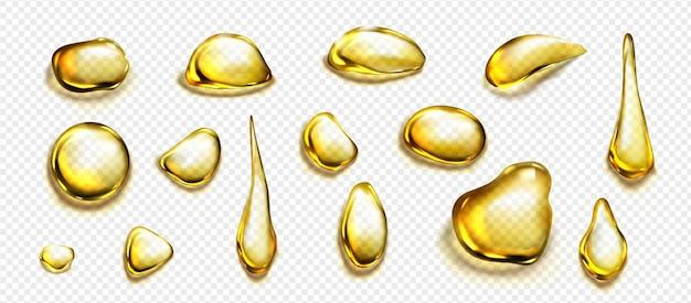 Золотые капли и лужи масла или жидкого меда, изолированные на прозрачном фоне. векторный реалистичный набор золотых капель органической косметики или пищевого масла, вид сверху четких желтых пятен Бесплатные векторы