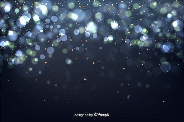 Golden particles background in bokeh style Free Vector