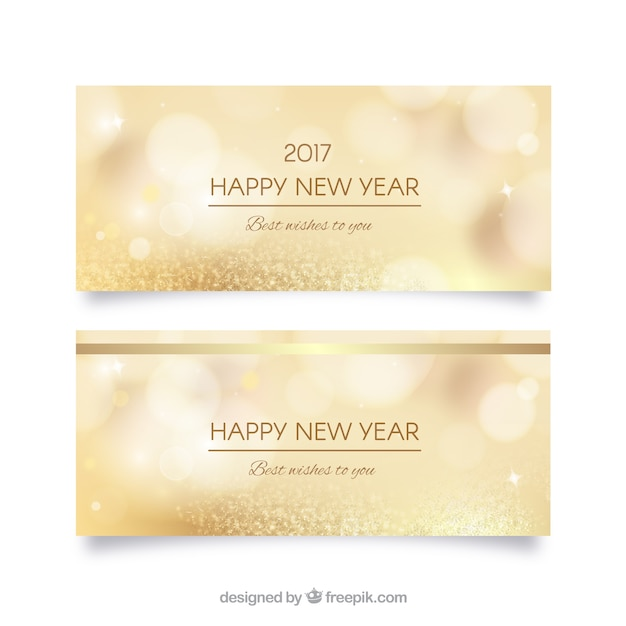 Golden unfocused new year banners Free Vector