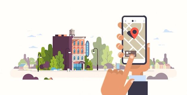 Рука смартфон концепция бронирования гостиницы здание хостел экстерьер мобильное приложение gps поиск точки на карте города городской пейзаж Premium векторы