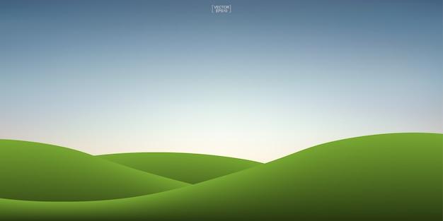 緑の草の丘と夕焼け空の背景 Premiumベクター