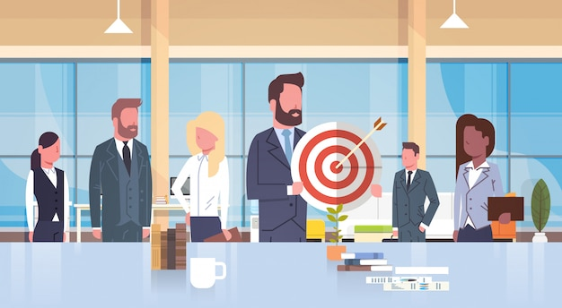 Group of business people holding target teamwork and strategy concept mix race team in modern office Premium Vector
