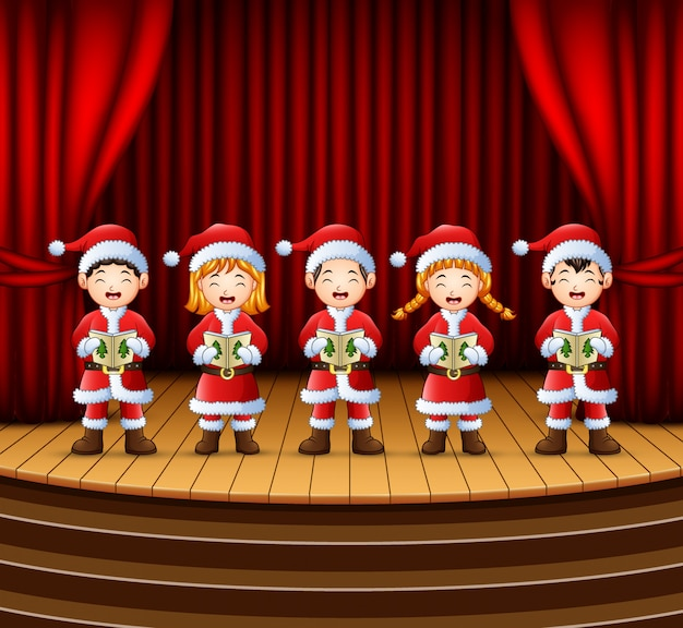 Christmas Carol Singers Figurines.Group Of Children Singing Christmas Carols On The Stage