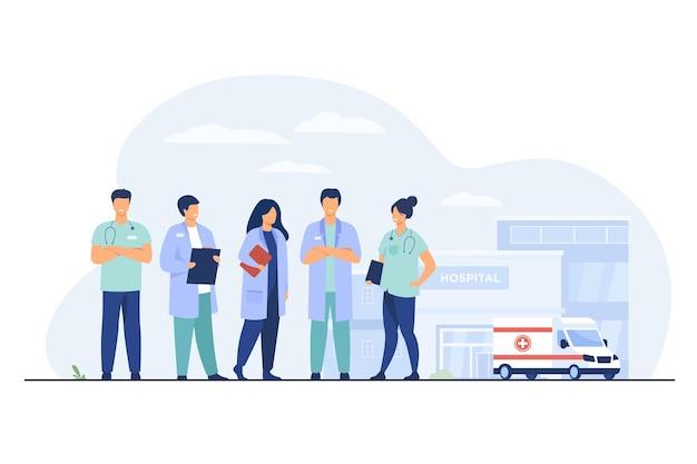 Gruppo di medici in piedi all'edificio dell'ospedale. squadra di praticanti e auto ambulanza Vettore gratuito