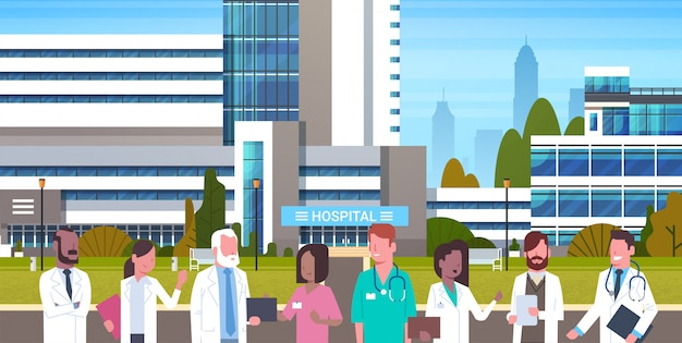 Group of medical doctors standing in front of hospital building exterior Premium Vector