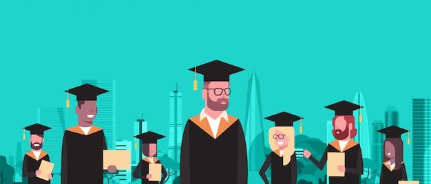 Группа студентов смешанной расы в выпускных кепке и мантии держит диплом за современные городские здания Premium векторы