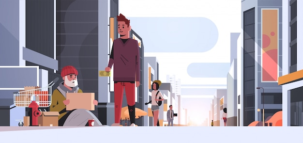 Guy giving money poor man sitting floor with belongings in trolley cart begging for help beggar holding sign board homeless modern city street sunset cityscape Premium Vector