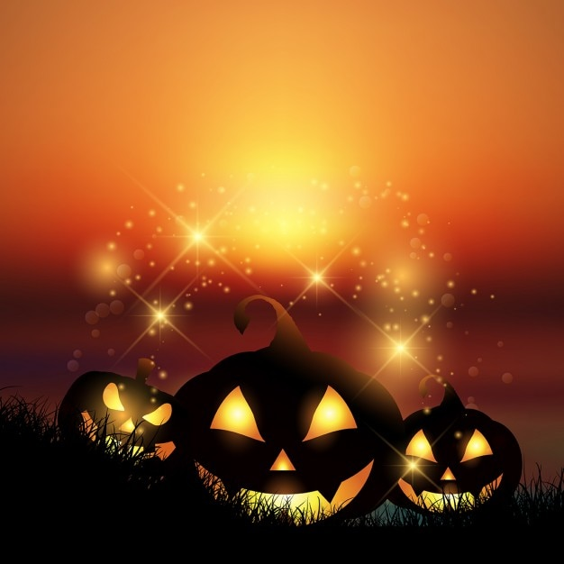 Halloween background with pumpkins against a\ sunset sky