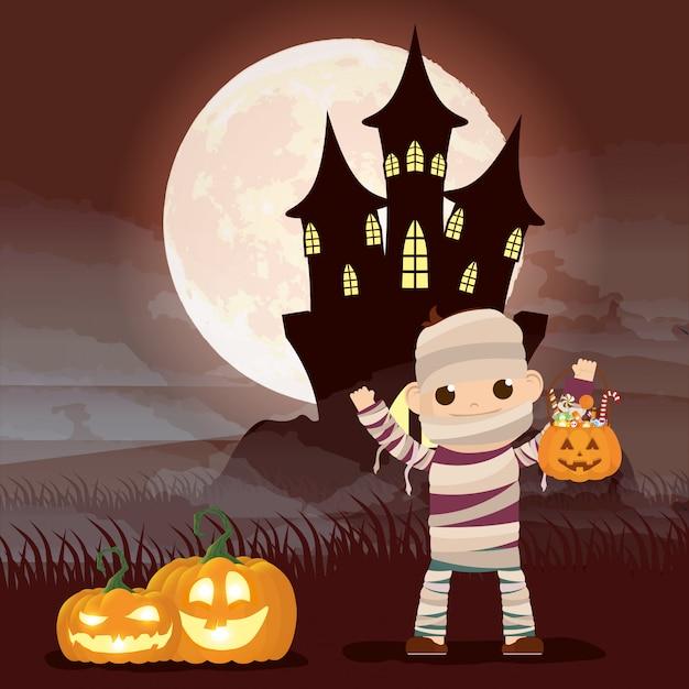 Halloween dark night scene with pumpkins and kid disguised mummy Free Vector
