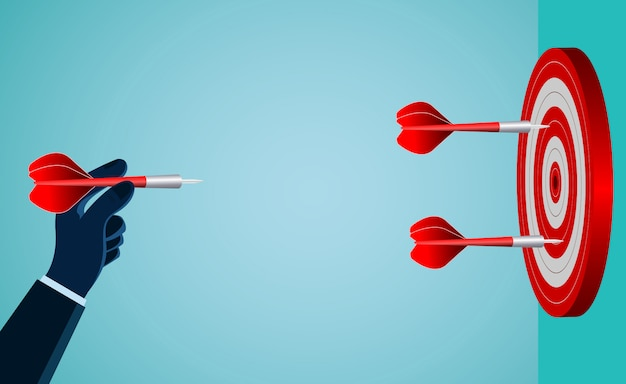 Hand of a businessman who is throwing a red dart to the target. Premium Vector