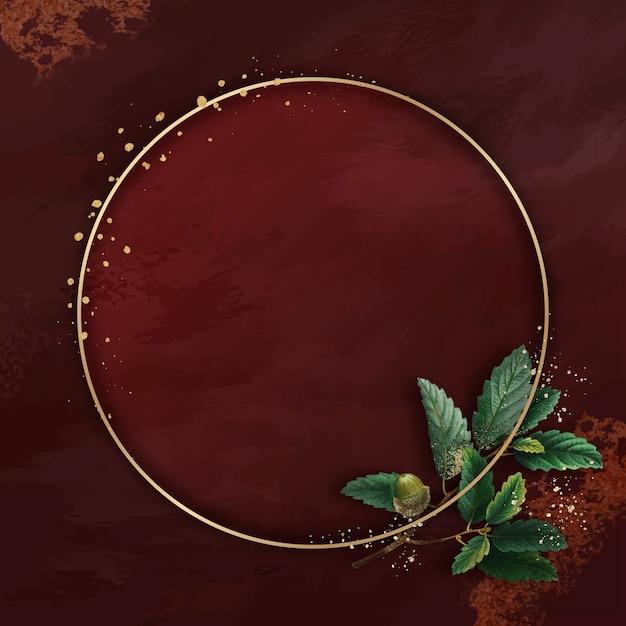 赤い背景の上の丸い金のフレームと手描きのオークの葉 無料ベクター