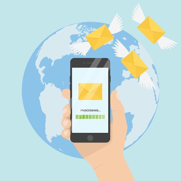 地球の背景に携帯電話を持っている手。メッセージを飛んでいる翼のアイコンが付いている手紙。 sms、電子メール、メッセージ、メールを送信します。 Premiumベクター