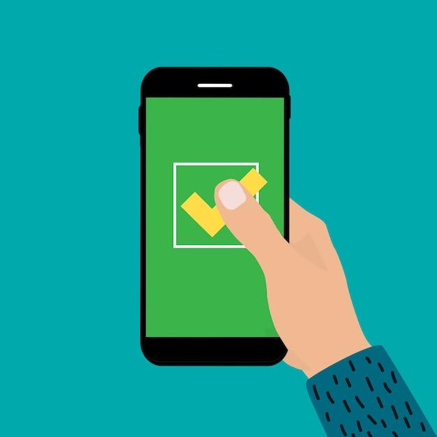 Рука, держащая мобильный телефон с знаком «да». Premium векторы
