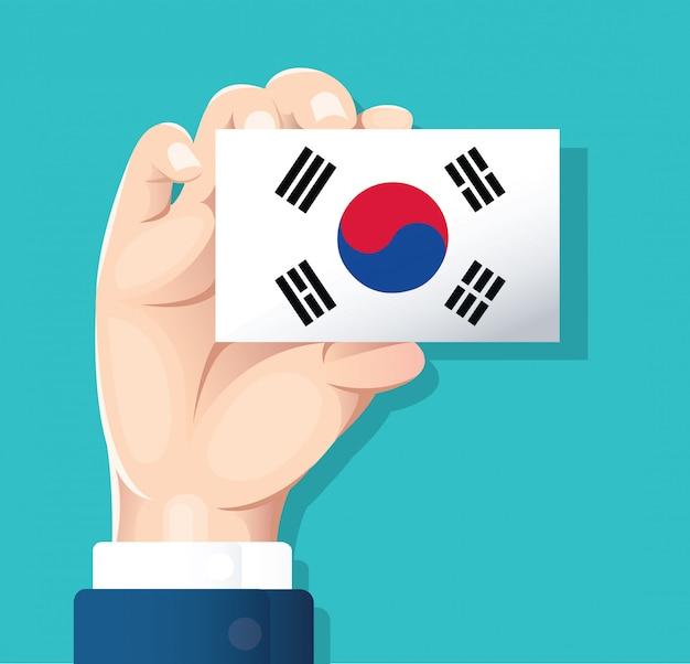 Hand holding south korea flag card Premium Vector