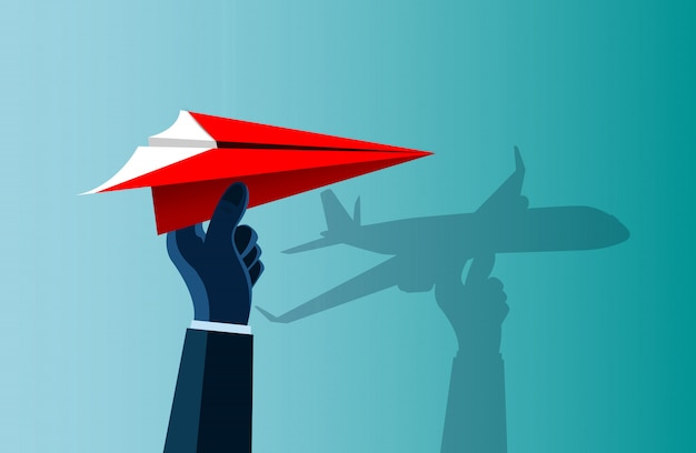 Hand human catching a red paper plane with a shadow on the wall as an airplane Premium Vector