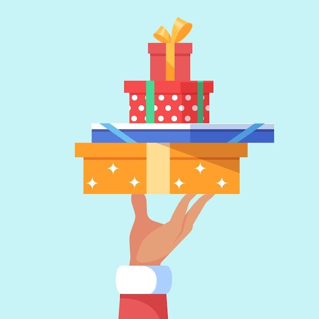 多くのクリスマスギフトボックスの大きなスタックを保持しているサンタクロースの手。 Premiumベクター