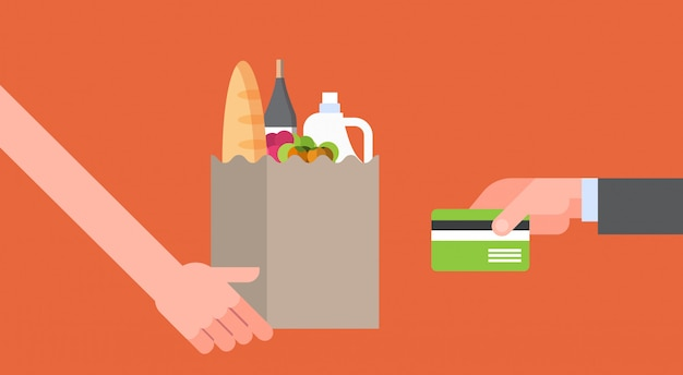 Hand paying for paper bag full of grocery products with credit card, online food order and delivery service concept Premium Vector