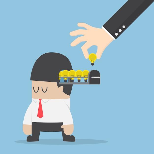Hand pick up light bulb of idea from businessman head Premium Vector