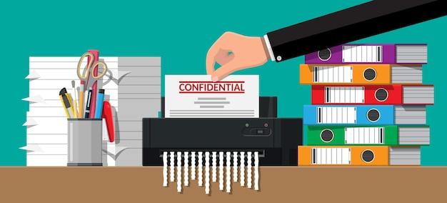 Рука положить документ бумагу в шредер. документ разорван в клочья. Premium векторы
