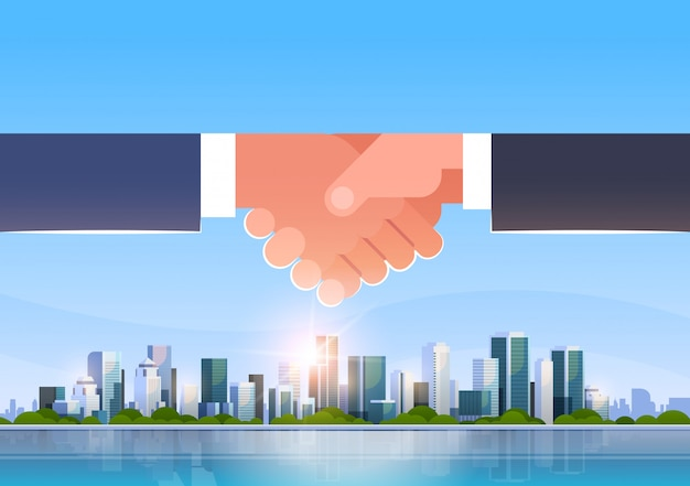 Hand shake over city skyline Premium Vector