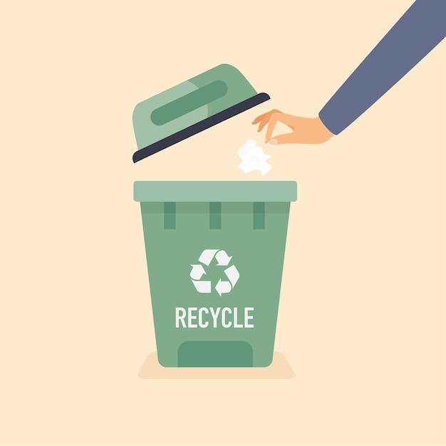 古紙をゴミ箱に捨てる手。リサイクルの概念。 Premiumベクター