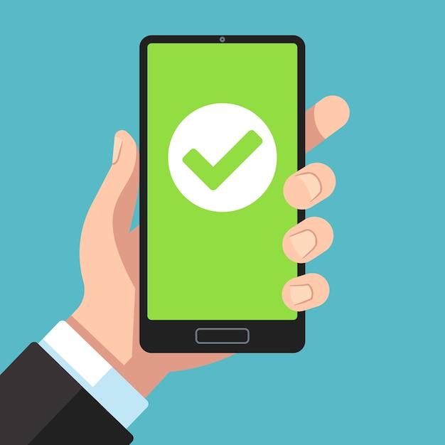 緑のチェックマークが付いたハンドヘルドスマートフォン Premiumベクター