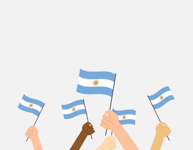 Hands holding argentina flags Premium Vector