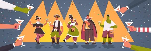Руки держат очки вокруг людей в разных костюмах, празднующих счастливую вечеринку в честь хэллоуина Premium векторы